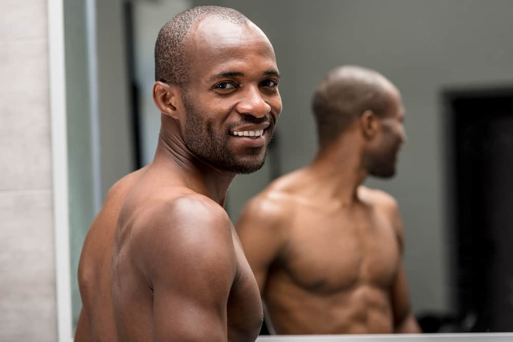 Man is looking in the mirror and smiling after shaving his black facial hair.