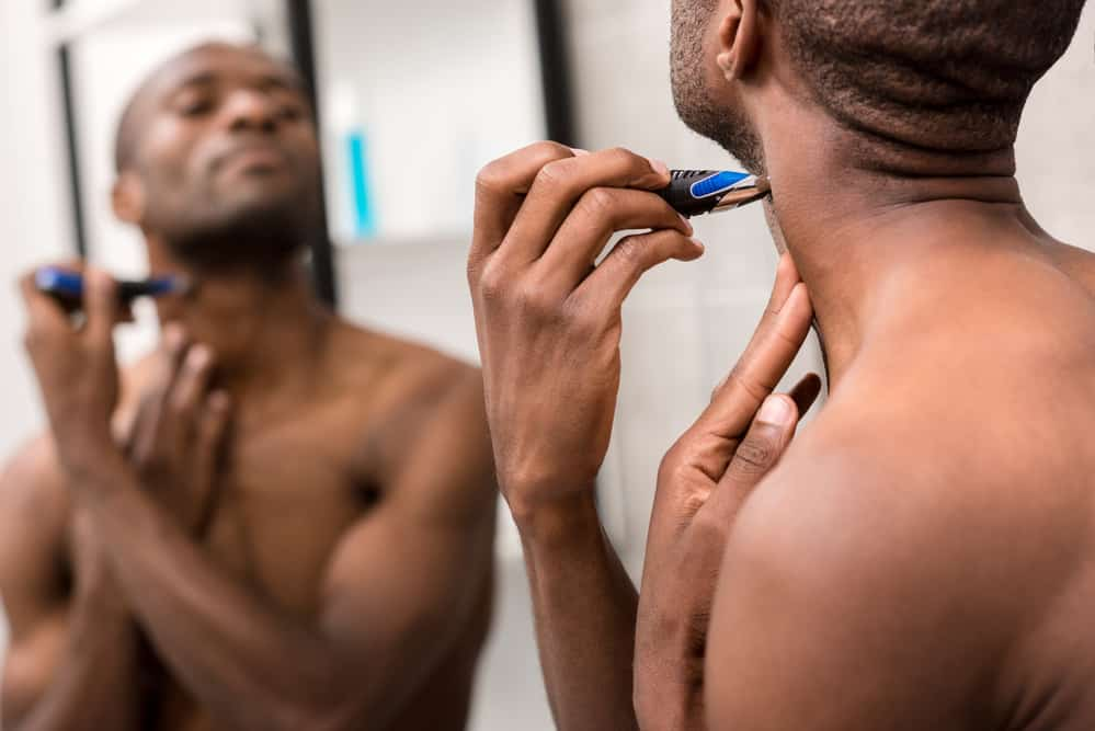 Black man trimming his own hair with a WAHL stainless steel lithium trimmer head.