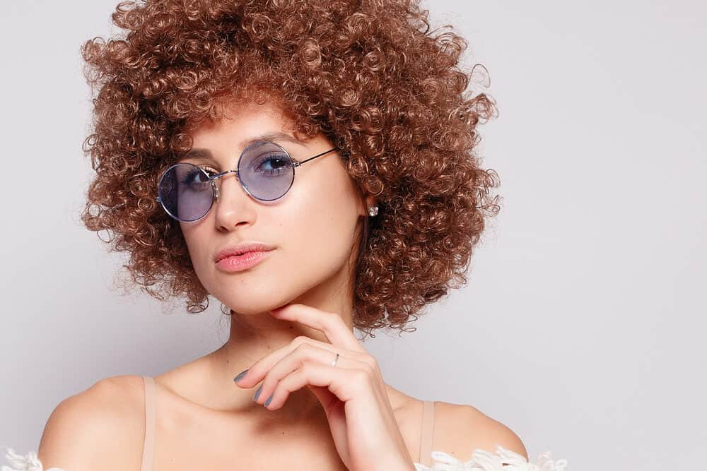 Beautiful lady with light brown brassy hair and a pale yellow skin tone wearing blue-tinted glasses and diamond earrings