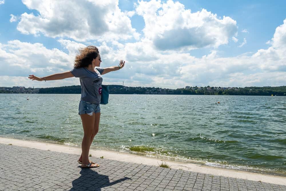 Lady dancing on a brick walkway at the lake as the brick fades into water.