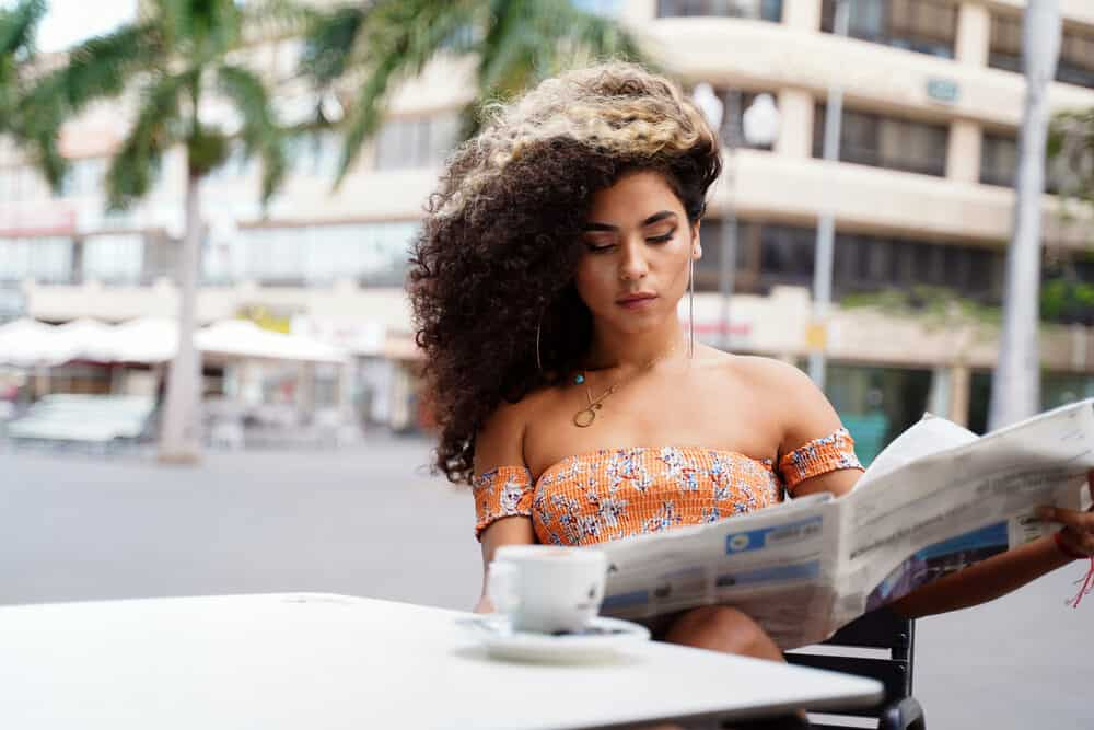 Beautiful woman reading a newspaper, while wearing hoop earrings and drinking a smooth liquid drink.