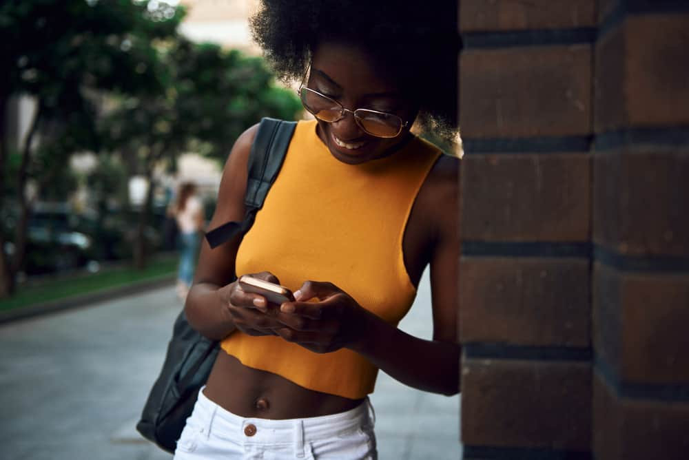 Woman with black natural hair wearing glasses and standing next to a brick wall while talking on her phone.
