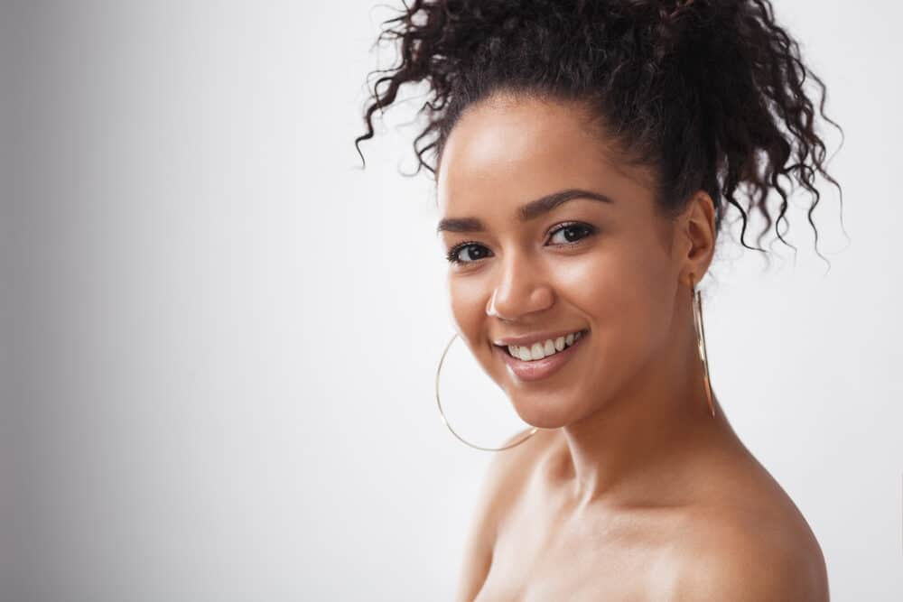 A light-skinned lady wearing neutral makeup preparing to start the curly hair method for wavy girls