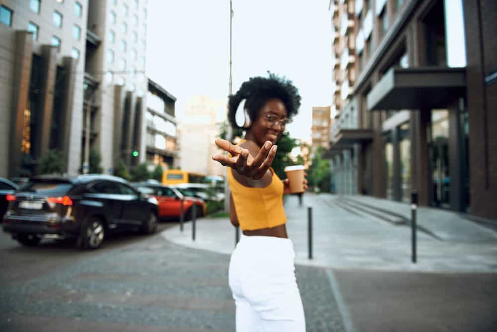 Cute black girl with naturally wavy hair wearing a yellow shirt and white pants.