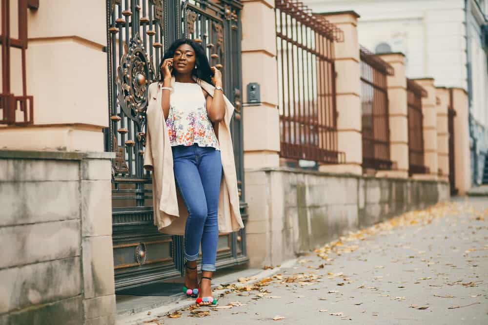 Lady standing outside with jet black hair talking on a mobile phone wearing casual fall clothes