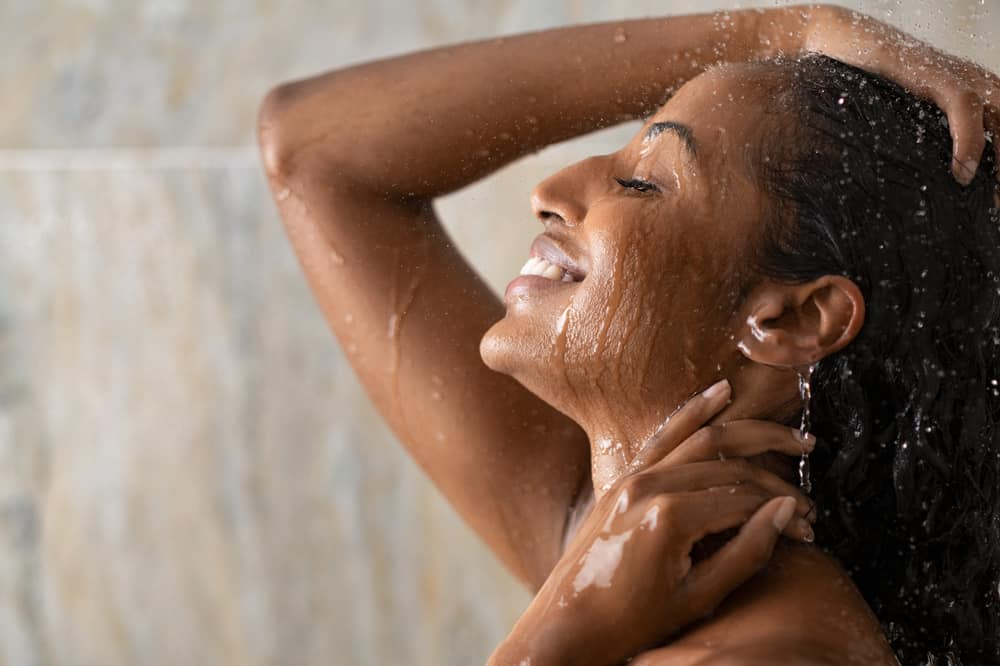 A young female with colored-treated hair using a hydrating shampoo bar to wash her hair in the shower.