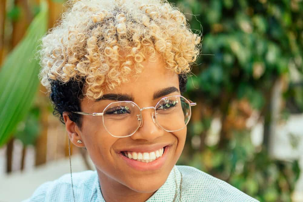 In the tropical park, a happy Afro-Latin female is seen wearing stylish eyewear and semi-permanent hair color