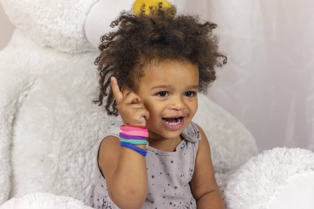 African American toddler with slime infested hair while coloring a picture