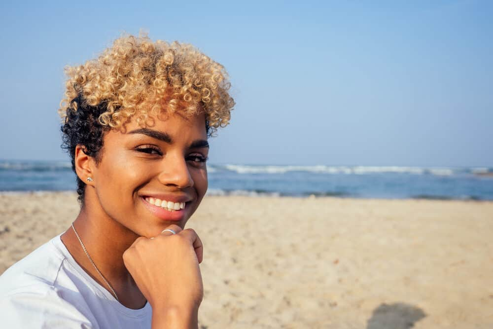 Young Latin female with black and blonde colored hair posing for a photo at the beach