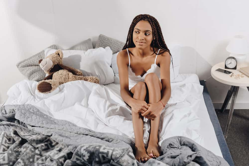 Cute woman with multi-colored sitting in the bed.