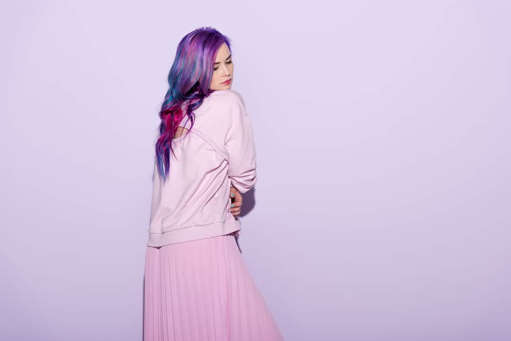 Female wearing a pink sweater and skirt with a dark purple faded hair color with a blue undertone.