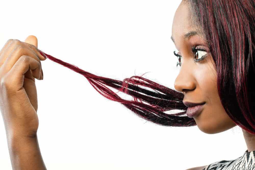 Cute black girl holding her Kool-Aid affected hair cuticles.