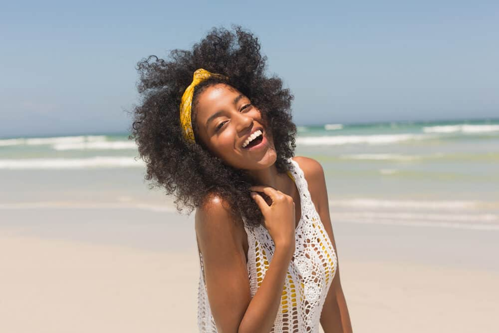 Black girl with curly hair and light caramel skin wearing a yellow swimsuit