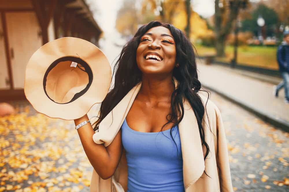 Lady outside with straight hair on a fall day smiling as the wind blows leaves around her