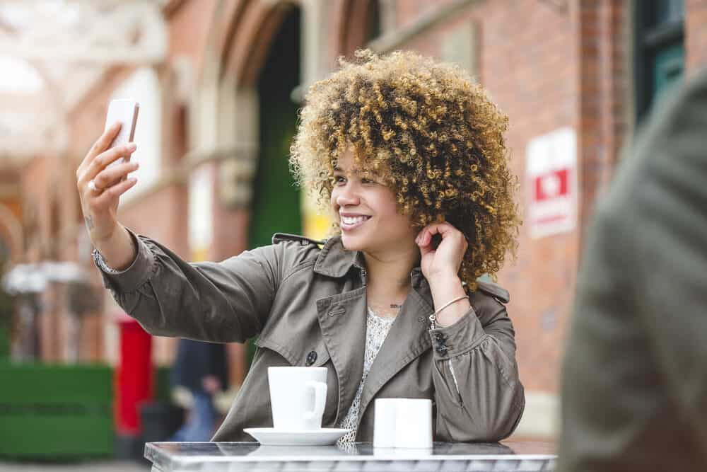 A woman taking a selfie with her smartphone at an outside café.