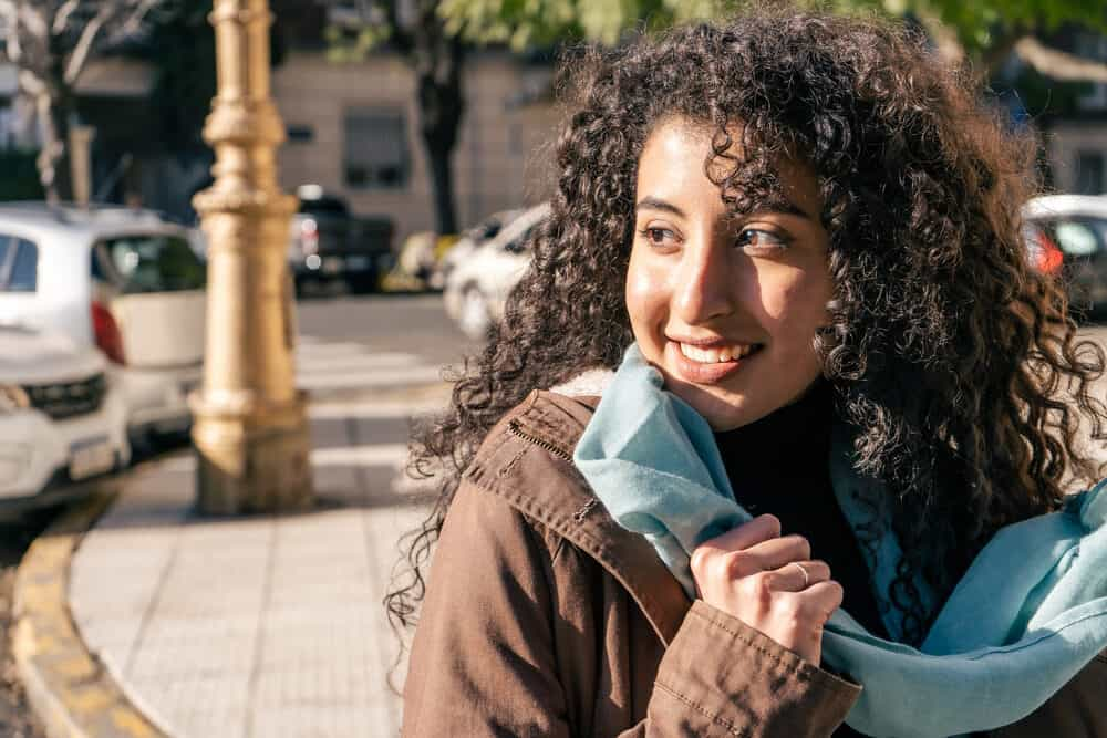 A beautiful Latin woman with curly hair strands looking into the distance while smiling