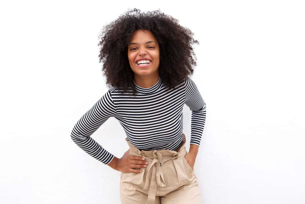 African American female with an even length hairstyle in its curly state wearing a black and white striped shirt and beige pants.