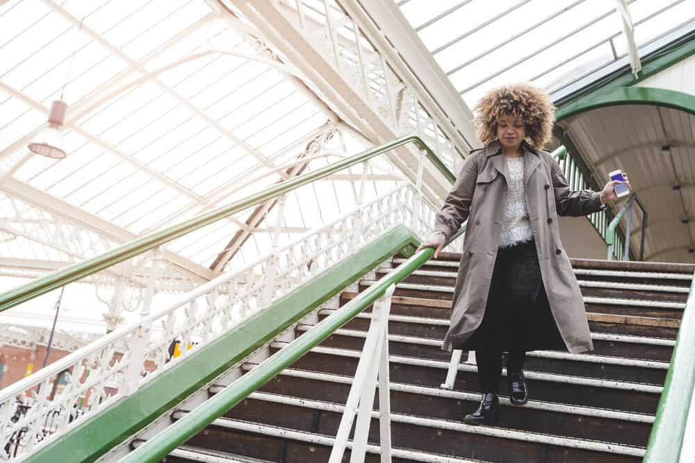 Black woman with curly tresses rushing downstairs with her phone in hand.