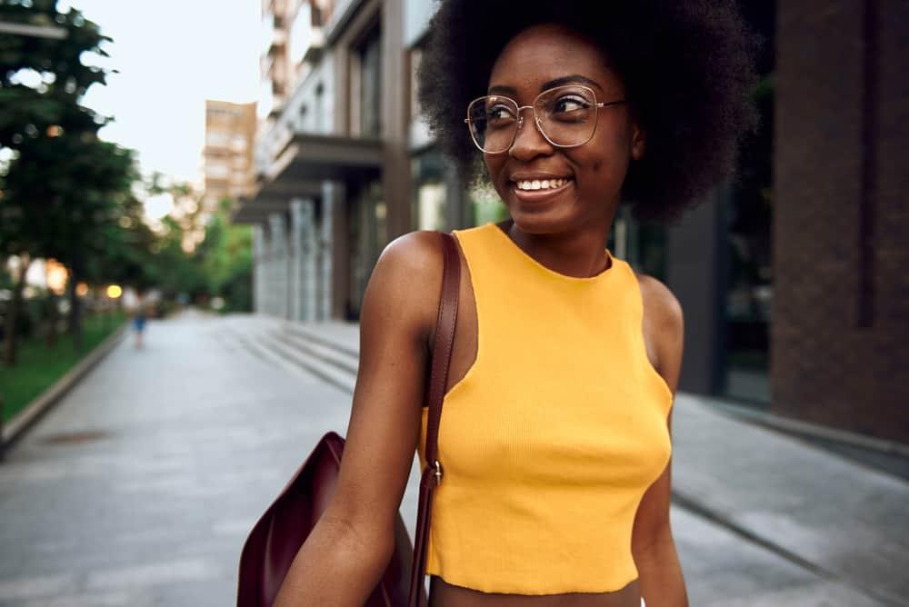 A joyful woman in a casual yellow shirt carrying a bag as she strolls through the city wearing glasses.