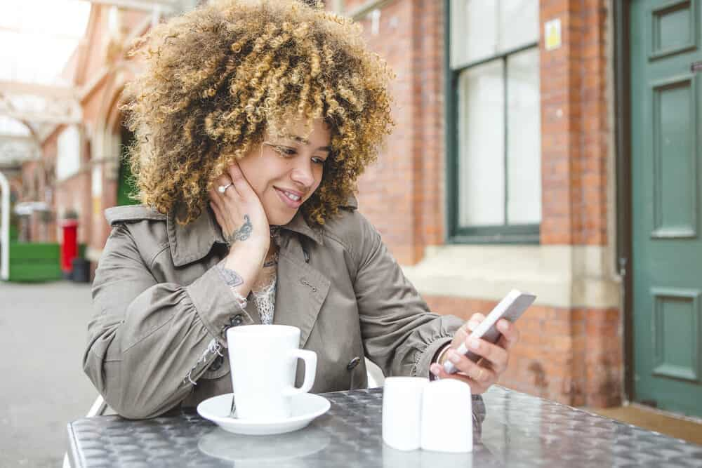 A woman with a beautiful curly hair type sitting outside at a cafe with a cup of coffee.