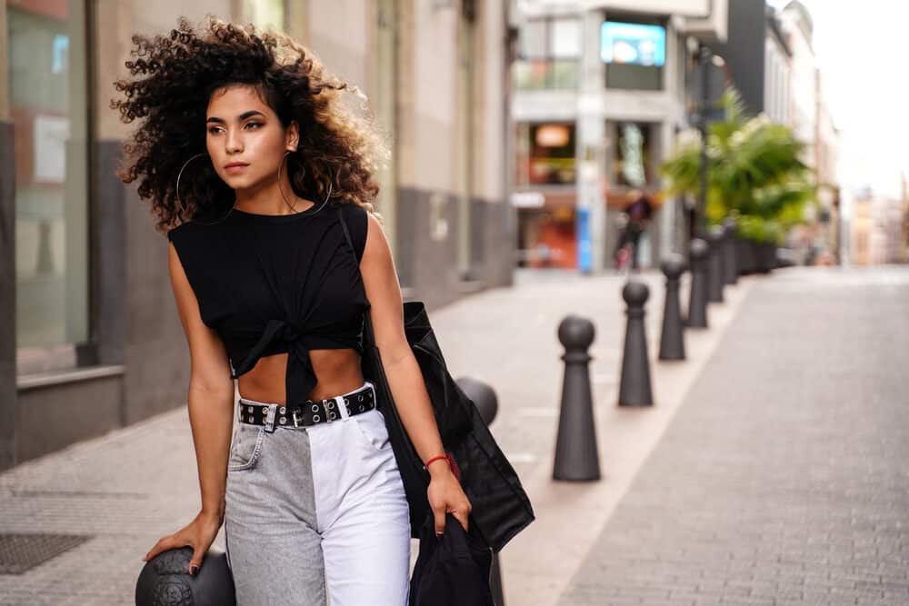 Young Colombian female with a unique style wearing large hoop earrings, a black t-shirt, and gray and white jeans.