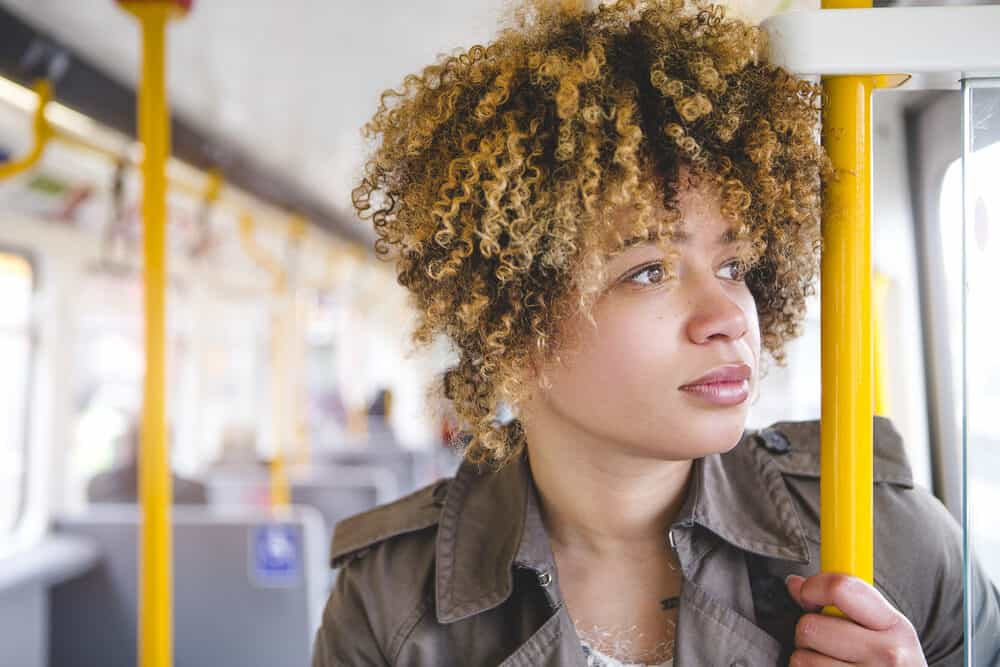 A woman with type 3 hair strands riding the subway is shown from a close-up while gripping the handrails and looking out of the window.