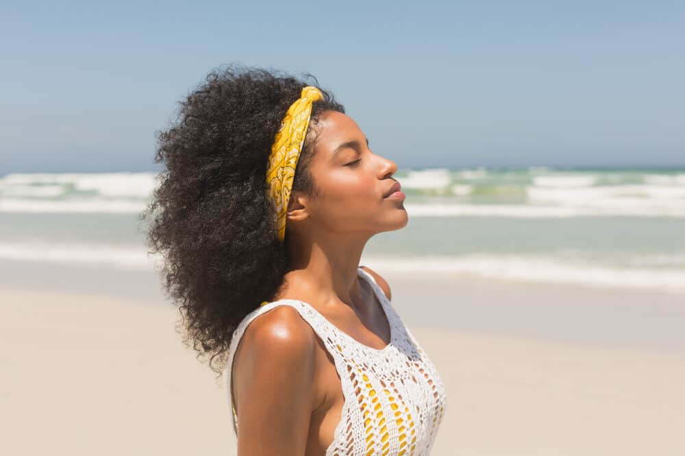 Cute African American lady with small frame body enjoying the fresh air at the beach