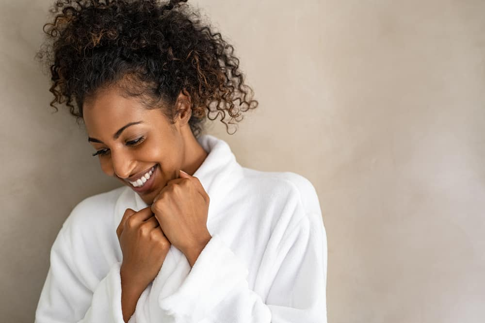 Beautiful young lady with curly dry hair in a white bathrobe after washing her hair strands with a Christophe Robin Hydrating shampoo bar with aloe vera.