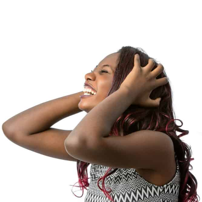 Black woman laughing as she holds her kool-aid dyed hair strands.