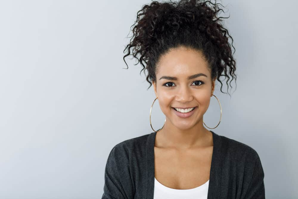 Black girl with hoop earrings wearing thick coarse hair treated with the wavy hair method