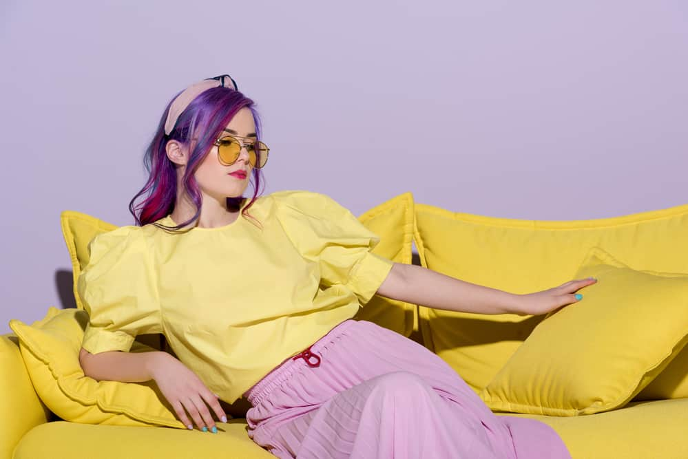 Caucasian women with faded Fuschia hair strands wearing a shirt with a bleach yellow tone and a pink ribbed skirt.