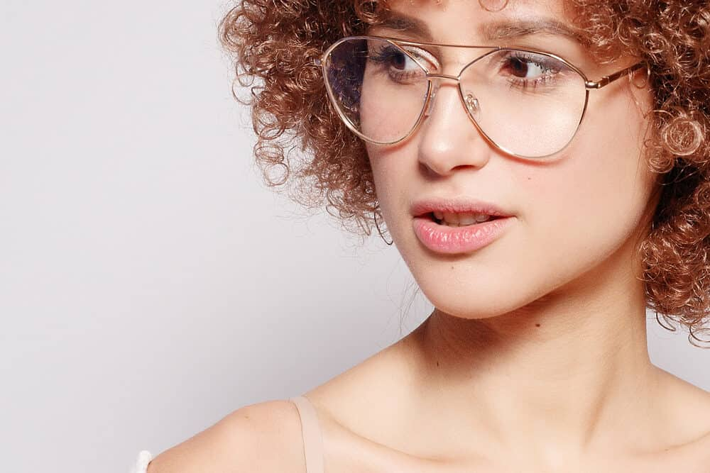 Young Caucasian woman wearing gold-framed glasses with darker hair and light skin-toned markup