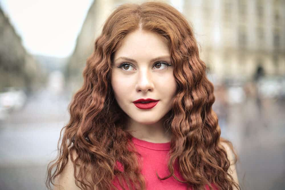 Cute female with a light perm and shoulder-length hair wearing red lipstick and neutral makeup.