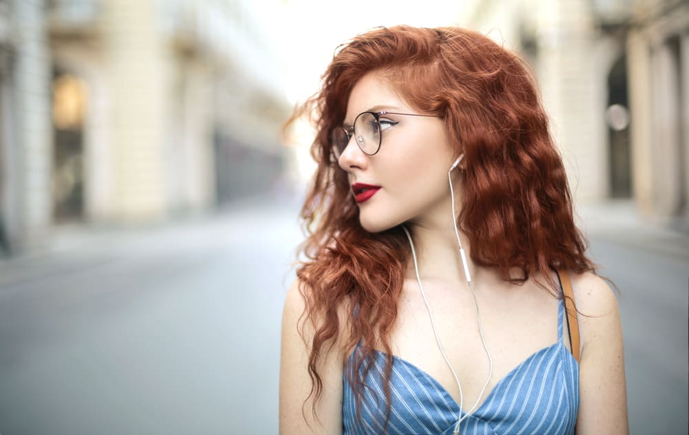 Female with very long hair wearing a blue dress while listening to music with white earphones.