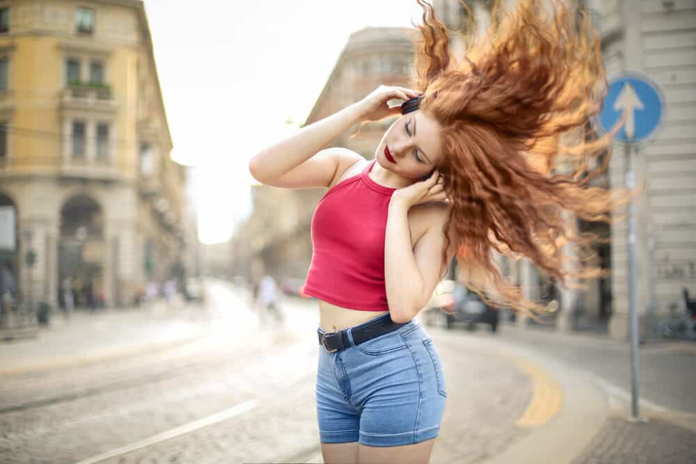 Woman dancing in the street with a tank top and blue jeans with a cute body perm.