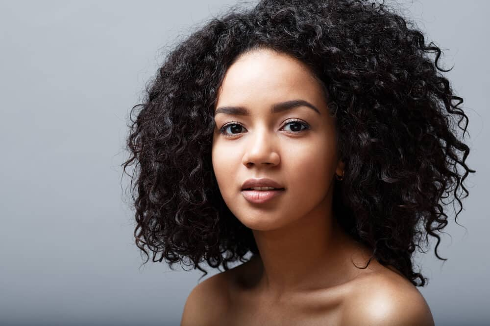 African American female with black wavy curly hair showing off her natural hair texture