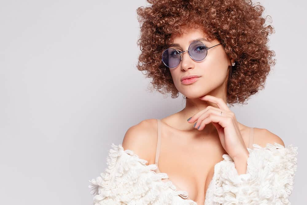 Young white female with a curly afro hairstyle on nicely toned hair with golden undertones and purple-blue tinted glasses