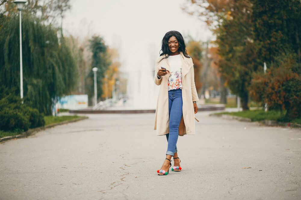 Black woman wearing a shirt with flowers, blue jeans, and a beige coat