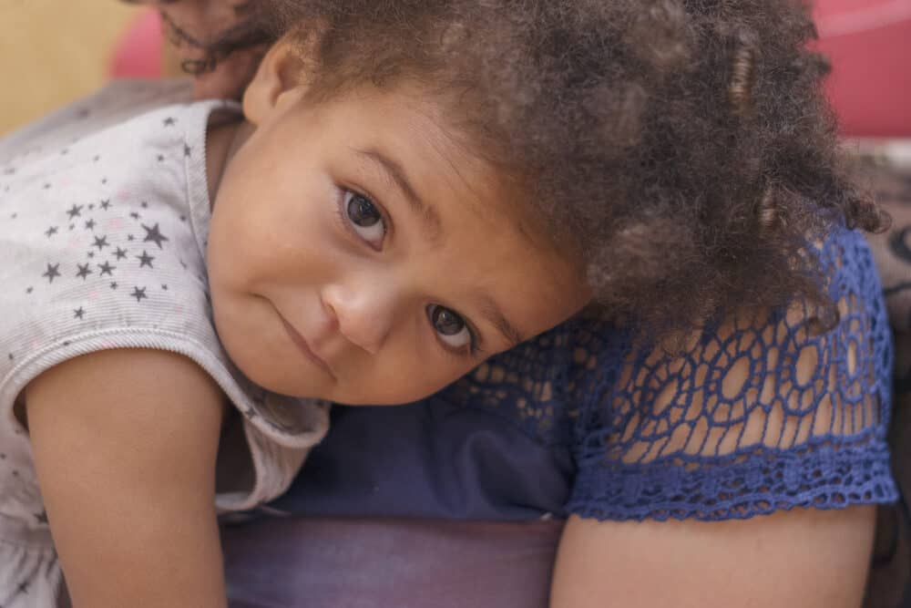 Cute African American girl laying on her mother's shoulder getting ready for a nap