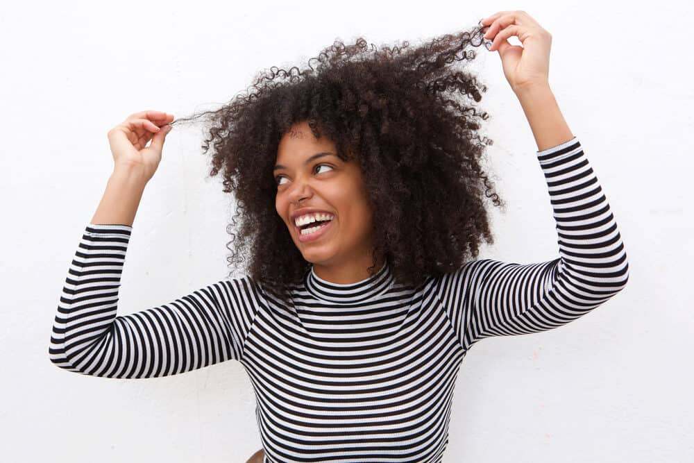 Black woman with a curly cut that highlights her type 3C and 4A curl patterns.