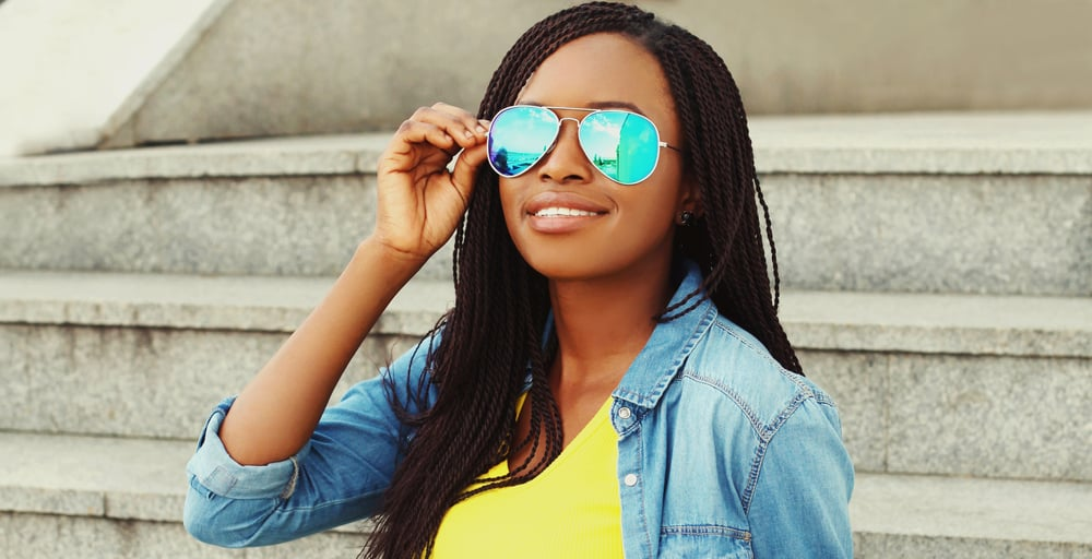 Black lady wearing shades and a great protective style on a 4C hair type