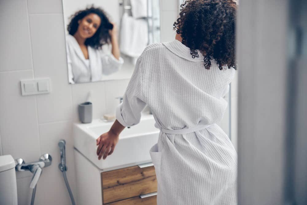 African American woman wearing a robe in the bathroom after towel drying hair