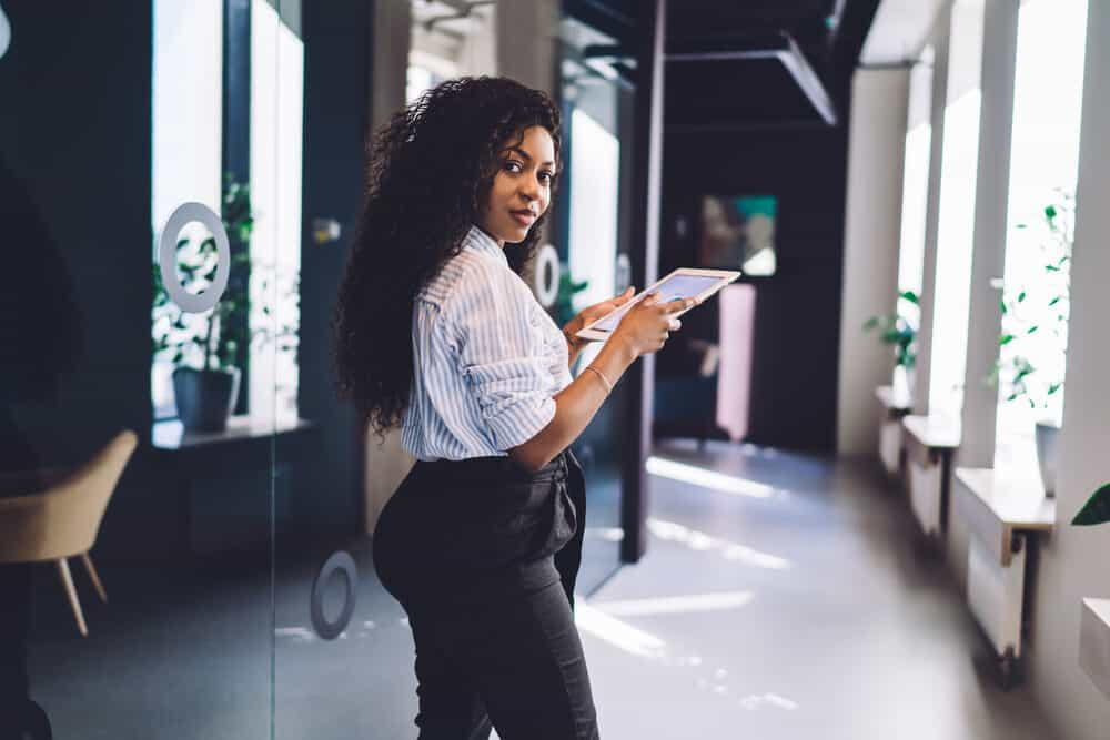 An attractive black employee with a mid-back hair length using an iPad at work