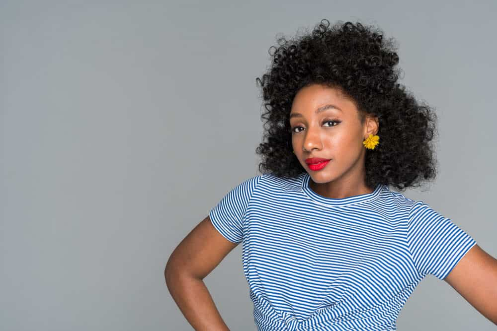 Black girl wearing a blue and white t-shirt, red lipstick, gold earrings, and a natural black hair color