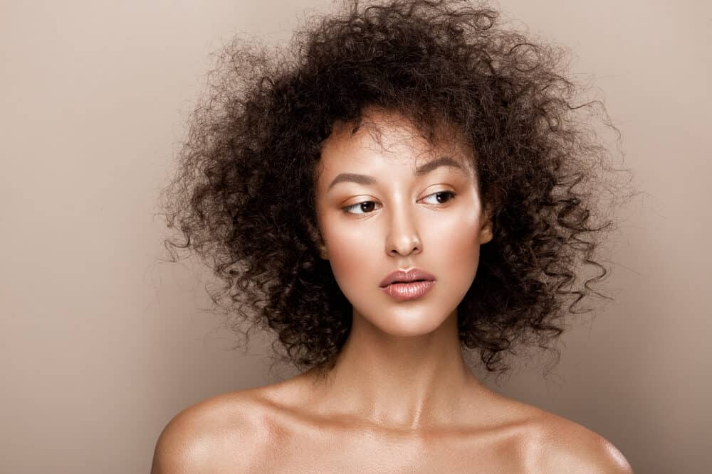 Black woman with thinning hair strands due to poor nutrition and oxidative stress
