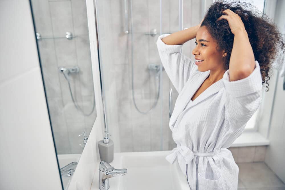 Beautiful young black girl air drying hair quickly after soaking strands in the shower
