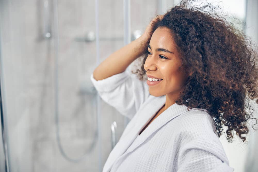 Pretty black woman with dark curly hair dried with a blow dryer adding a leave-in conditioner