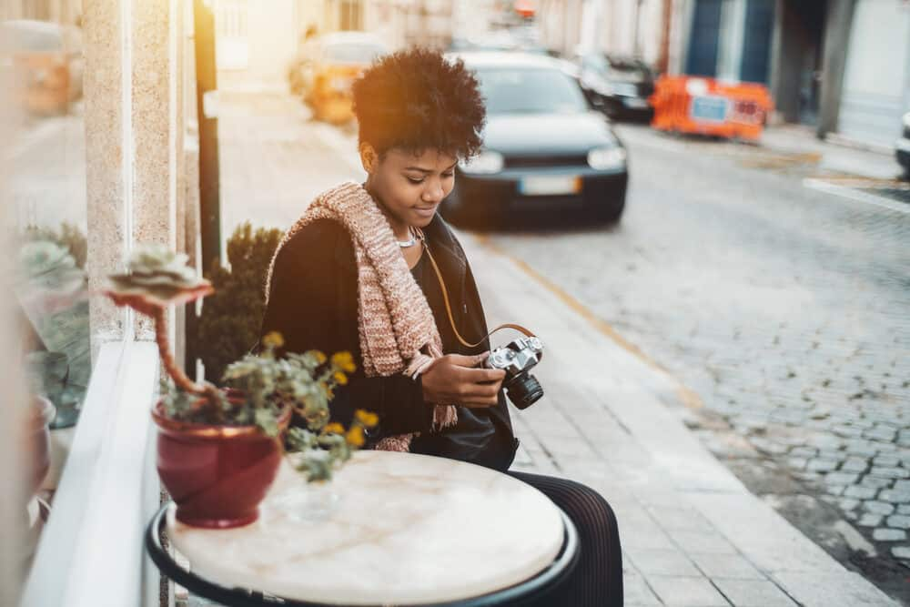 Cute Brazilian curly girl sitting outside a restaurant using a camera