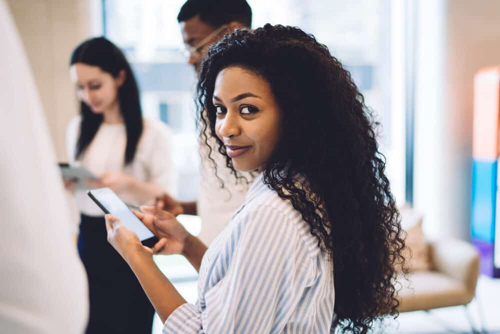 Black woman with medium length hair checking her phone at work with men and women in the background