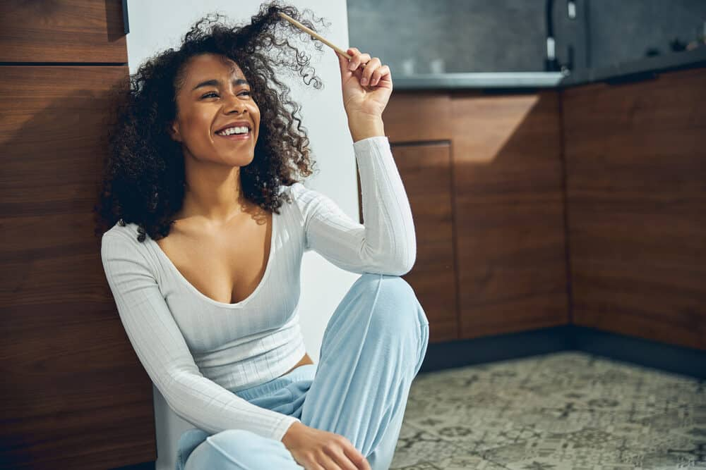 African American lady sitting on the floor in pajamas with curly dry hair with major frizz